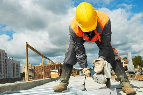 Construction worker with hard hat, uses a grinder