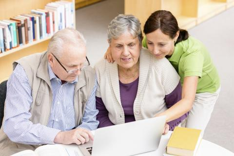 An older couple views content on a laptop while receiving assistance