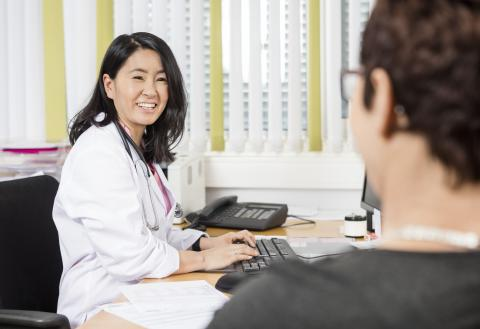Doctor uses the computer while interviewing patient