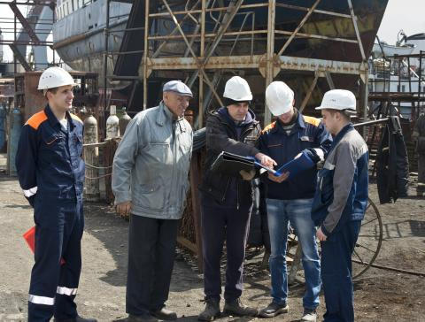 Engineers discuss plans at the shipyard