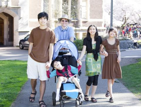 Family walk together outside on sidewalk