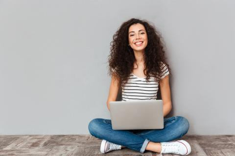 Female sitting on floor smiling with laptop