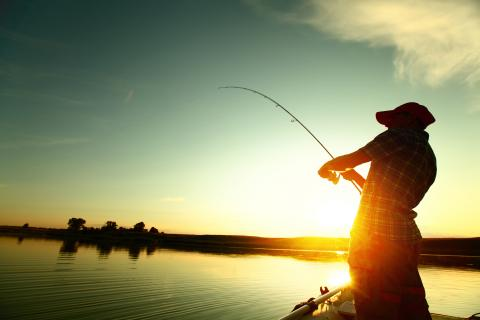 At sunset, an adult reeling in a fish on a boat.