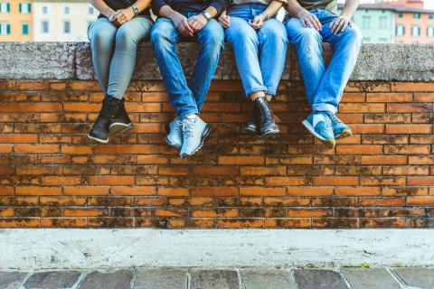 Four people in jeans sitting on a brick wall