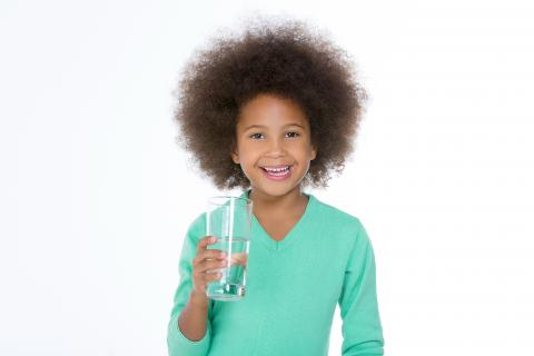 Girl holds a glass of water