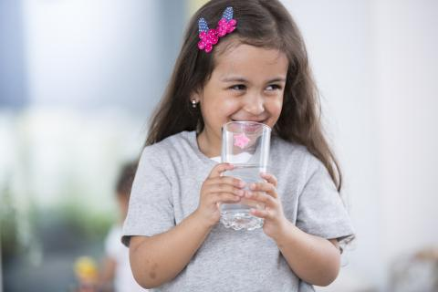 A child holds glass of water
