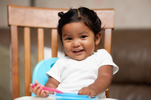 A smiling child sits in a high chair with a spoon and a bowl.