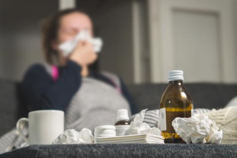 Ill woman blowing nose with used tissues and meds on table