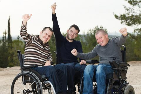 Three smiling men seated in wheelchairs