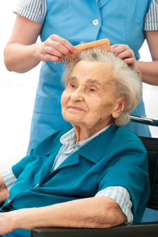 Elderly woman getting her hair combed
