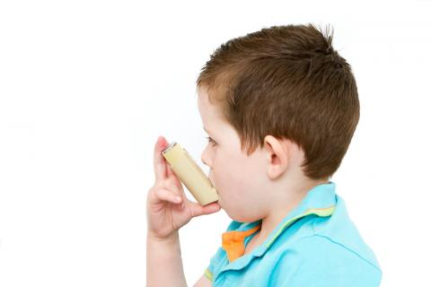 Young boy uses his inhaler