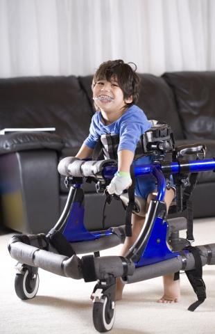 Young disabled boy using a specialty walker