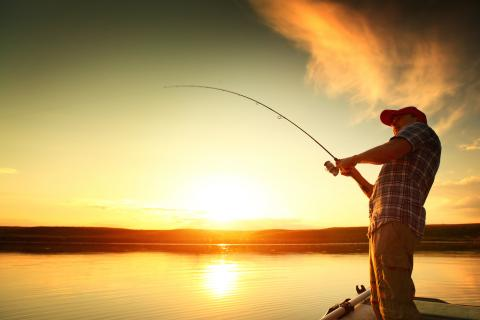 Man reels in a fish while the sun sets (or rises) on a lake