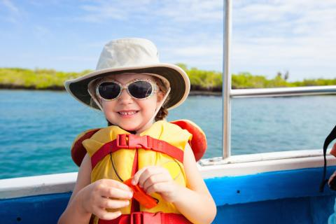 Young child wears a life vest, sun hat and glasses on a boat