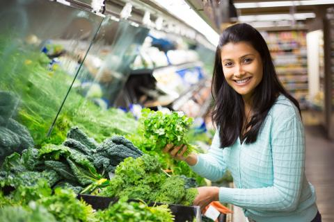 A person chooses cilantro among leafy greens at a grocery store