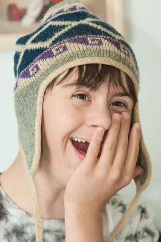 Happy teen wearing warm hat with his hand over his mouth