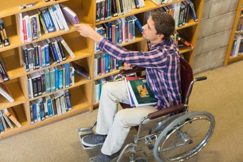 Teenage boy in wheelchair at the library