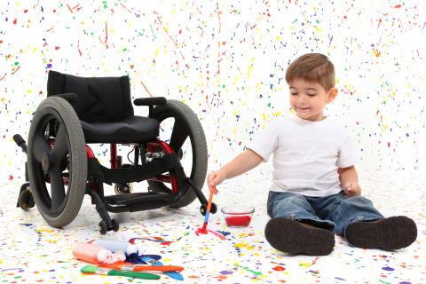 Child on the floor splatters paint a white room with a wheelchair close by