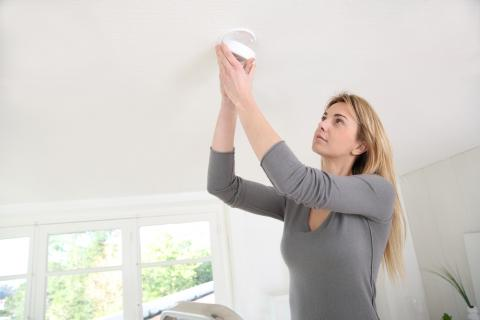 An adult checks a smoke detector in the ceiling.