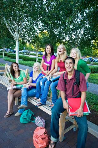 Group of teens sitting around a school bench
