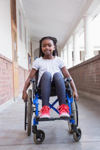 Smiling young girl seated in wheelchair