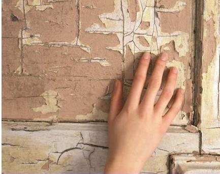 Image of a hand touching a severely flaked wall of lead paint.