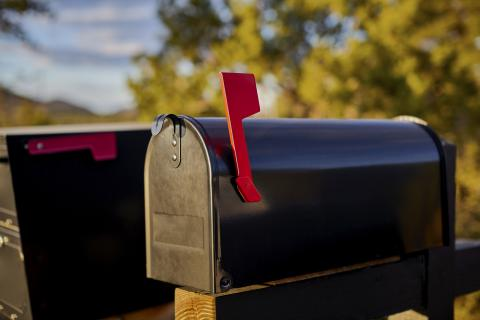 Black mailbox with red flag up