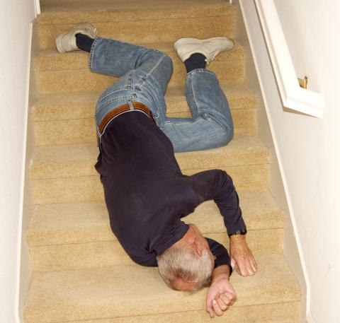 An unconscious adult lays on steps.