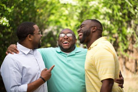 Three adults hugging and laughing outside.