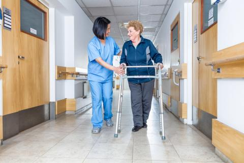 CNA assisting a senior use a walker down a hospital hallway