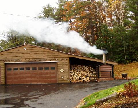 Garage with an outside wood burner and stack of logs