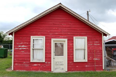Side of red shed type building with peeling paint and door.