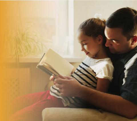 A father and daughter sitting together reading a book