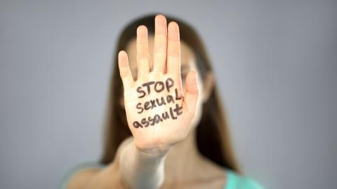 Adult woman with hand in front of face with Stop Sexual Assault written on it.