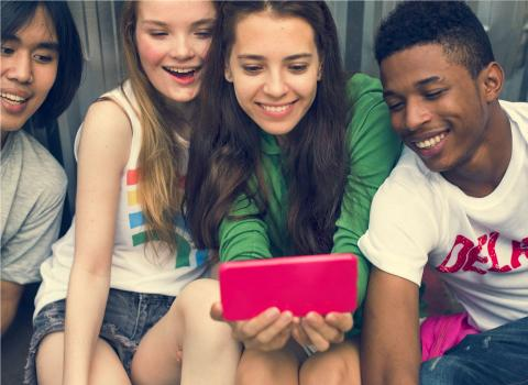 Four teens watching a cell phone