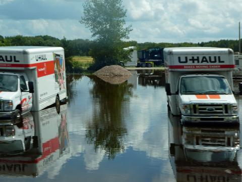 Trucks sitting in flooded parking lot.