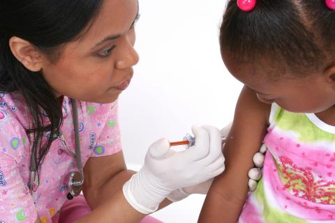 Young child is being vaccinated by a nurse