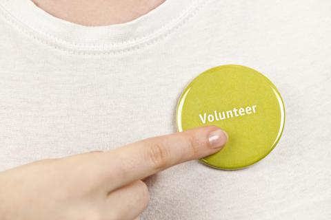 A finger pointing to a green button with word, volunteer pinned on a shirt
