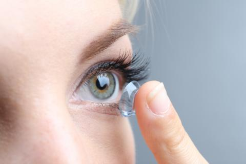 Closeup of woman inserting contact into eye