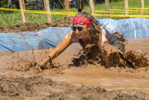 A smiling adult with sunglasses crawling through mud pit with water.