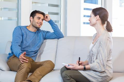Man on couch talking to a woman psychologist