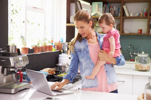 A mother holding a toddler checks her laptop while standing in the kitchen