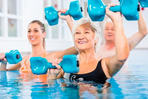 Three adults exercising with dumbbells in a swimming pool.