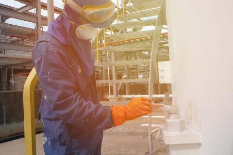 Worker wearing safety mask and protective clothing painting in manufacturing plant