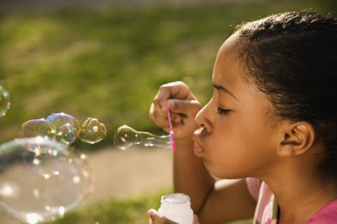 Young child blowing bubbles outside
