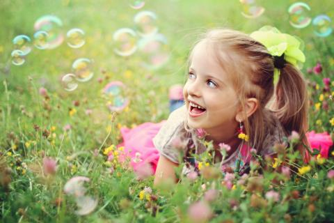 Young blonde haired girl playing outside with bubbles