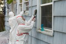 Two adults in hazmat suits removing lead paint from a building.