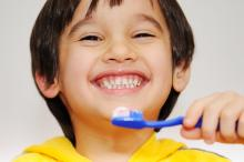 A portrait of a smiling child holding a toothbrush.