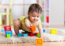 A toddler playing with blocks on an area rug at home