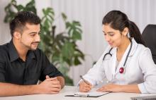 Doctor consulting with male patient in her office